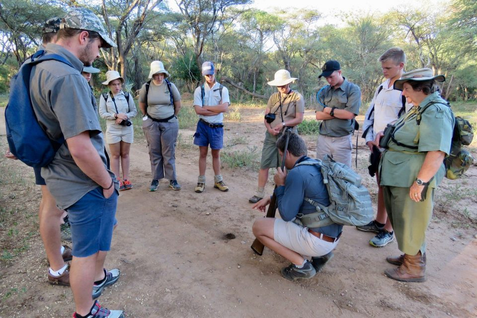 Professional guide Andy Smith discussing ants while the Peterhouse School Conservationist, Penny Raynor looks over his shoulder